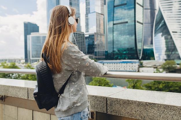 街で探してヘッドフォンで音楽を聞いて、ピンクのサングラスとバックパック、春夏の都会的なスタイルを着て通りで楽しんでいる流行に敏感な若い女性