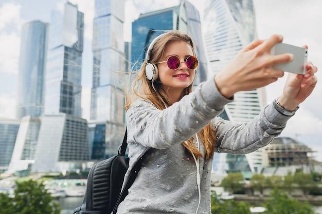 ヘッドフォンで音楽を聞いて、ピンクのサングラス、春夏の都会的なスタイル、スマートフォンで自分撮り写真を撮って通りで楽しんでいる流行に敏感な若い女性