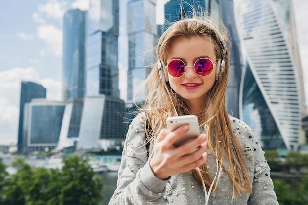 Молодая хипстерская женщина веселится на улице, слушая музыку в наушниках, в розовых солнцезащитных очках, в весеннем летнем городском стиле, используя смартфон