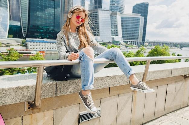 Молодая хипстерская женщина веселится на улице, слушая музыку в наушниках