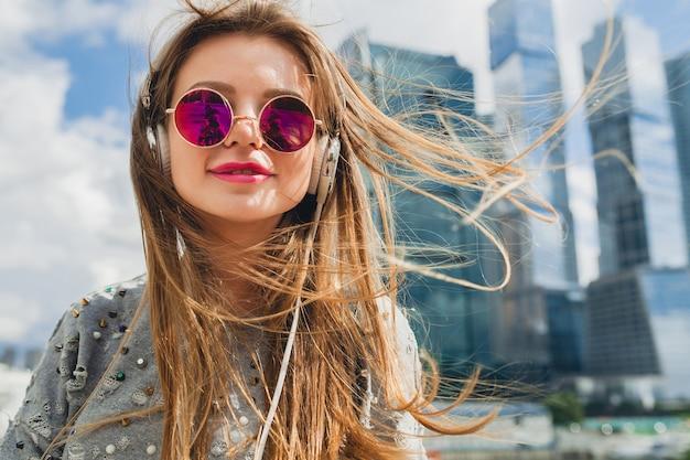 ヘッドフォンで音楽を聴いてストリートで楽しんでいる若い流行に敏感な女性