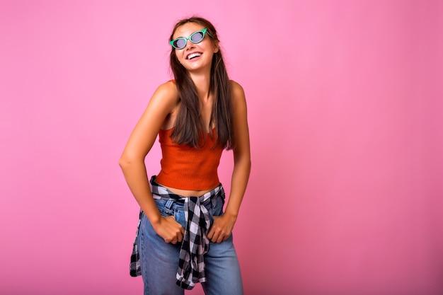 Молодая хипстерская женщина с удовольствием показывает язык и позирует