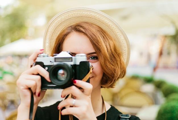 レトロなカメラを手に持って写真を撮る流行に敏感な若い女性