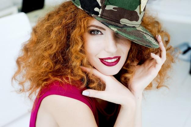 笑顔のウェーブのかかった髪の帽子の若い流行に敏感な女性