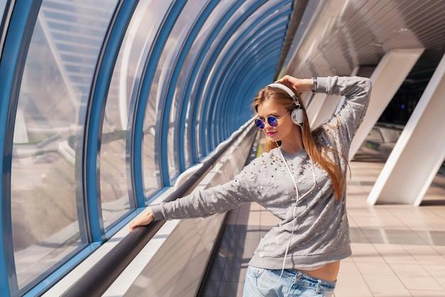 Молодая хипстерская женщина в повседневной одежде веселится, слушая музыку в наушниках, в джинсах, свитере и солнцезащитных очках, городской стиль