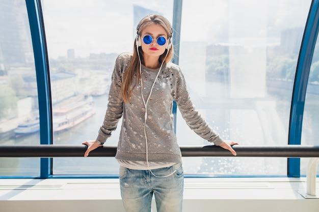 ヘッドフォンで音楽を聴いて楽しんでいるカジュアルな服装の若い流行に敏感な女性