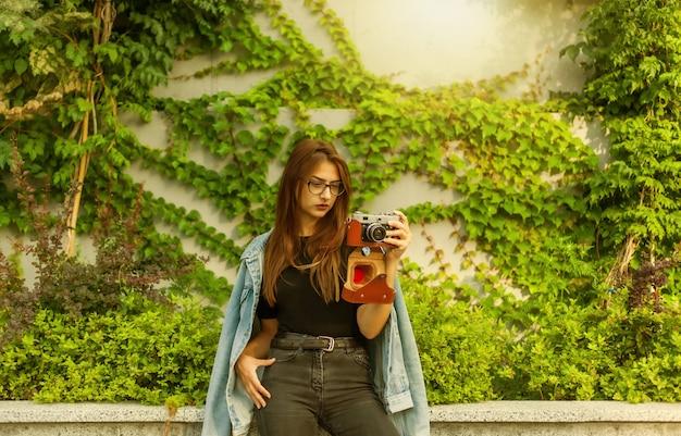 デニムジャケットとメガネの若い流行に敏感な女性は、屋外でフィルムレトロカメラを楽しんでいます