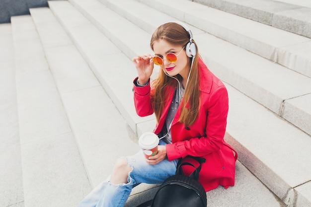 サングラスをかけているピンクのコート、ジーンズのバックパックとコーヒーをヘッドフォンで音楽を聞いて通りの若い流行に敏感な女性