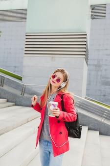 Молодая хипстерская женщина в розовом пальто, джинсах на улице с рюкзаком и кофе, слушает музыку в наушниках