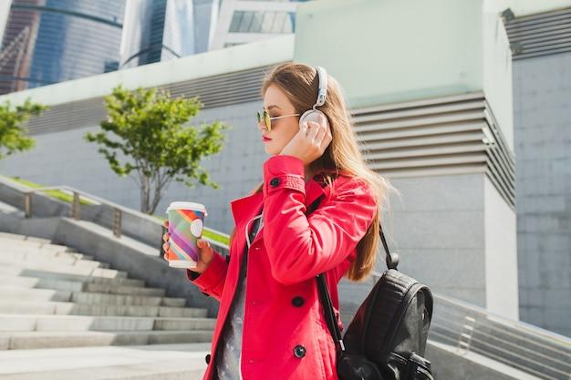 ピンクのコートを着た若いヒップスターの女性、バックパックとヘッドフォンで音楽を聴いているコーヒーと通りのジーンズ