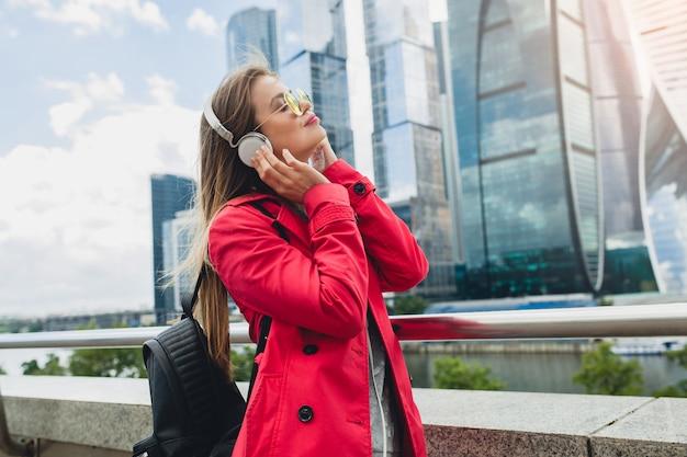 Молодая хипстерская женщина в розовом пальто, джинсах на улице с рюкзаком, слушает музыку в наушниках, в темных очках