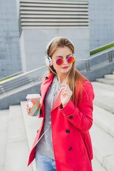 Молодая хипстерская женщина в розовом пальто, джинсах на улице с кофе, слушает музыку в наушниках, в темных очках