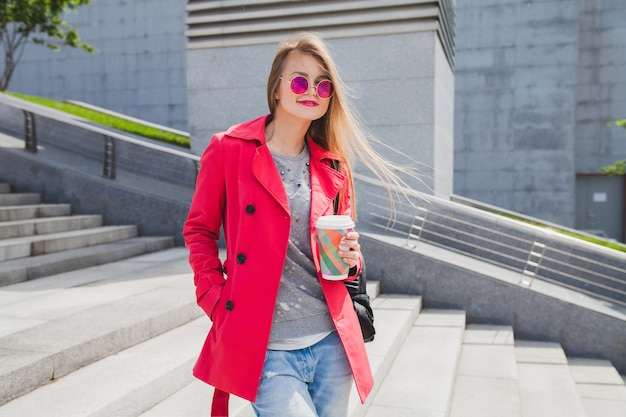 Молодая хипстерская женщина в розовом пальто, джинсах на улице с кофе, слушая музыку в наушниках