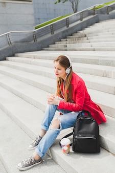 ピンクのコート、ジーンズのバックパックとヘッドフォンで音楽を聞いて、大都市の都市春スタイルのトレンドが付いている通りに座っている若い流行に敏感な女性