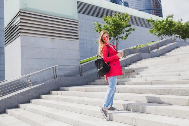 Молодая хипстерская женщина в розовом пальто, джинсах, идущих по лестнице на улице с рюкзаком и кофе, слушает музыку в наушниках, в темных очках