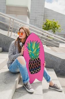 セーターとジーンズを身に着けているバランスボードと通りのピンクのサングラスの若い流行に敏感な女性