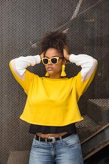 Молодая хипстерская женщина в модном наряде и солнцезащитных очках