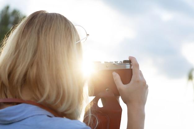 파란색 셔츠를 입은 젊은 힙스터 여성 사진가가 석양에 빈티지 필름 카메라로 사진을 찍고 있습니다. 텍스트를 위한 공간