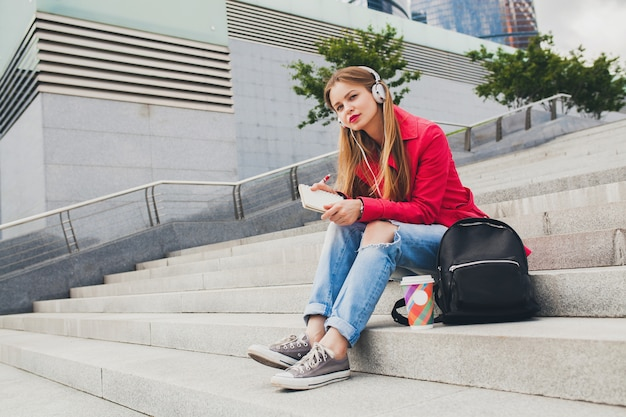 Young hipster woman in pink coat, jeans sitting in street with backpack and coffee listening to music on headphones, student making notes