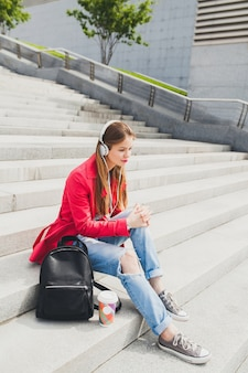 Young hipster woman in pink coat, jeans sitting in street with backpack and coffee listening to music on headphones