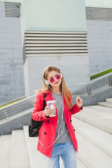 Young hipster woman in pink coat, jeans in street with backpack and coffee listening to music on headphones, wearing sunglasses