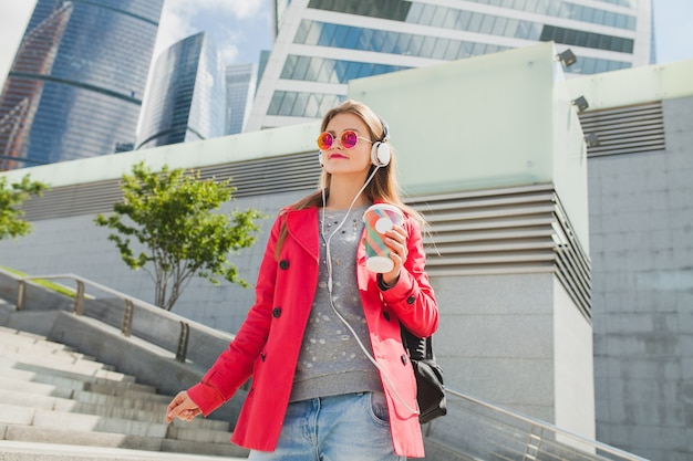 Young hipster woman in pink coat, jeans in street with backpack and coffee listening to music on headphones