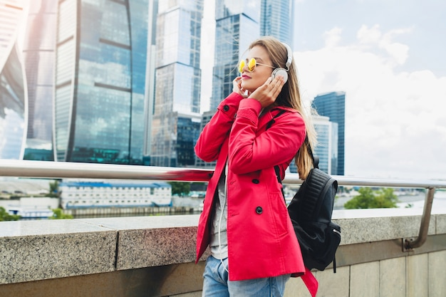 Young hipster woman in pink coat, jeans in street with backpack listening to music on headphones