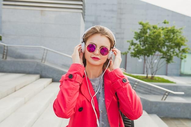 Donna giovane hipster in cappotto rosa, jeans in strada con caffè ascoltando musica in cuffia