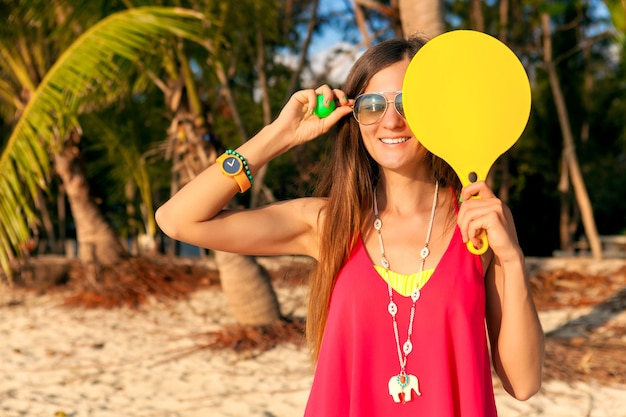 Young hipster woman playing ping-pong on tropical beach, summer vacation.