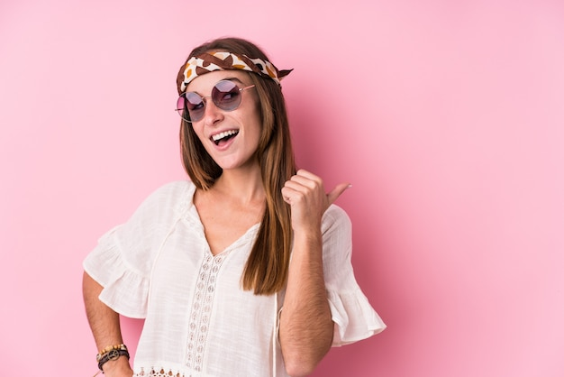 Young hipster woman points with thumb finger away, laughing and carefree.
