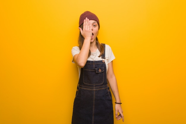 Young hipster woman shouting happy and covering face with hand