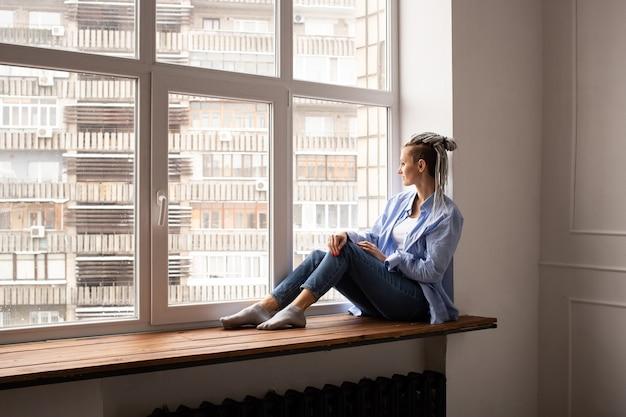 젊은 hipster 여자는 창턱에 앉아있다. 집에서 혼자 격리. 코로나 바이러스 테마. 집에서