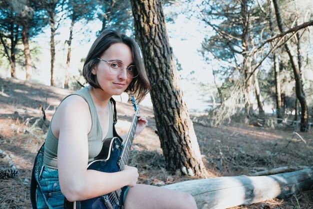Битник молодая женщина, сидящая в стволе, играя на гитаре на фоне парка или сада. девочка-подросток учится играть песни и писать музыку. хобби, образ жизни, отдых, инструмент, досуг, концепция образования