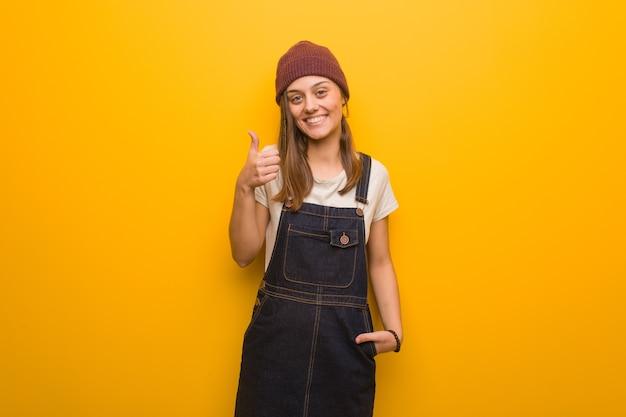 Битник молодая женщина улыбается и поднимает палец вверх