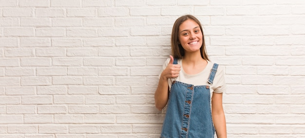 Young hipster woman smiling and raising thumb up