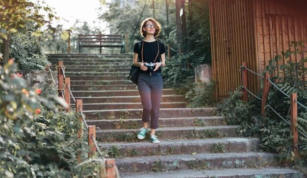 屋外の階段の上の公園でレトロなカメラで歩く若い流行に敏感な女性観光客