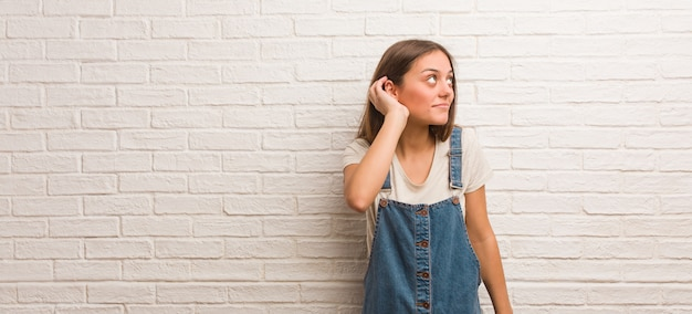 Young hipster woman try to listening a gossip