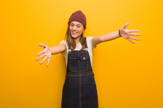 Young hipster woman very happy giving a hug to the front