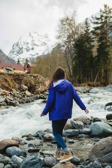 冬の森の川で岩の上を歩く若い流行に敏感な女性