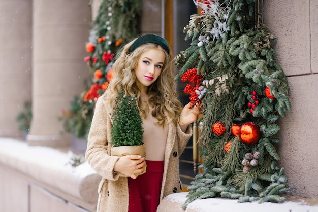 A young hipster woman walking through the citys snowcovered streets holds a potted