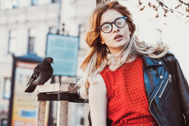 Young hipster woman wearing red dress  in the city. spring and birds doves.