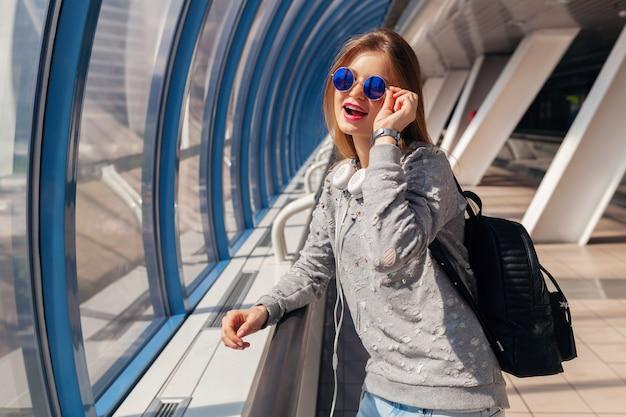 ジーンズ、セーター、サングラスを身に着けているカジュアルな服装に身を包んだ都市の近代的な建物でバックパックを持つ流行に敏感な若い女性