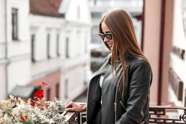 街で休んでいる流行のサングラスでスタイリッシュな黒の革のジャケットに茶色の長い髪の若い流行に敏感な女性。かわいい笑顔の元気な女の子が週末を楽しんでいます。