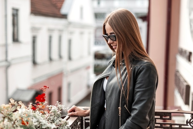 Young hipster woman with brown long hair in a stylish black leather jacket in trendy sunglasses resting in the city. cheerful girl with a cute smile enjoys the weekend.