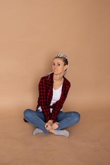 베이지 색 벽에 고립 된 험 상을 가진 젊은 hipster 여자