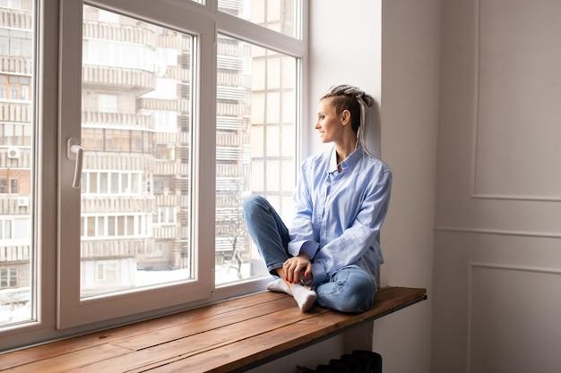 창턱에 앉아 험 상을 가진 젊은 hipster 여자. 코로나 바이러스 테마. 집에있어.