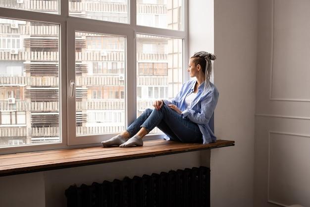 창턱에 앉아 험 상을 가진 젊은 hipster 여자