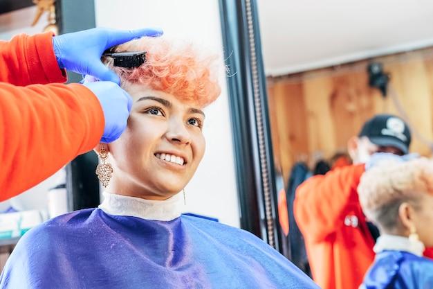 ピンクの髪を染めた流行に敏感な若い女性は、フェイスマスクと保護手袋を身に着けているプロのスタイリストによって彼女の髪をカットされます。