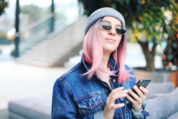 ピンクの髪と帽子を持つ若い流行に敏感な女性