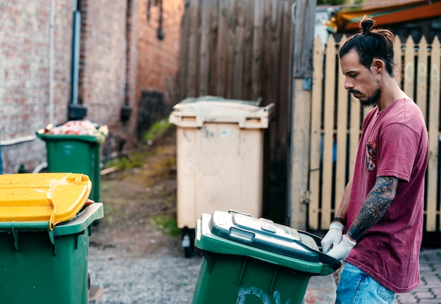 A young hipster young male concerned about environment is pushing the full rubbish wheelie bins on the street to be collected